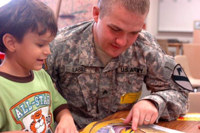 Sgt. Thomas Labrie reads along with 5-year-old Cris Luna a pre-kindergarten student, at Maxdale Elementary School in Killeen, Texas, during the schools literacy day Sept. 8. Four 'Greywolf' Soldiers spent two hours with pre-K students reading various children's books. Labrie is an Arabic linguist with Rear Detachment, 3rd Special Troops Battalion, 3rd Heavy Brigade Combat Team, 1st Cavalry Division, who hails from Vernon, Conn.