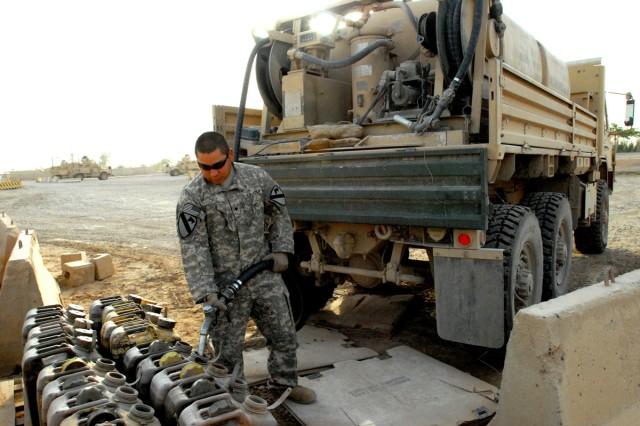BAGHDAD - Spc. Israel Cruz, a fuel supply specialist, from Floresville, Texas, fills up five-gallon containers at a coordinated fuel point at Victory Base Complex, here, Sept. 8.  Some of the fuel points maintain generators for signal operations, making sure radars and communications equipment coordinate effectively, said Cruz, of Headquarters Support Company, Division Special Troops Battalion, 1st Cavalry Division.