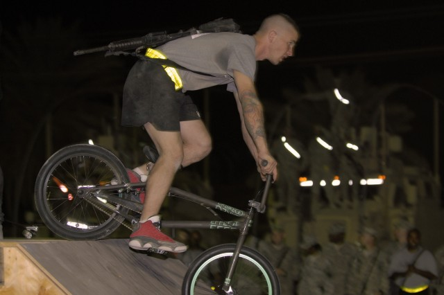 """CAMP LIBERTY, Iraq - Spc. Gary Keane, a light-wheeled vehicle mechanic with the 50th Expeditionary Signal Battalion, 160th Signal Brigade, rides his new BMX bike off a ramp after receiving it as a gift from pro BMX and skateboard athletes at the show, Bikes Over Baghdad, in Camp Liberty, here, Sept. 9. """"This is seriously a dream come true,"""" said the Raleigh, N.C., native. """"This is seriously the greatest day of my life."""""""
