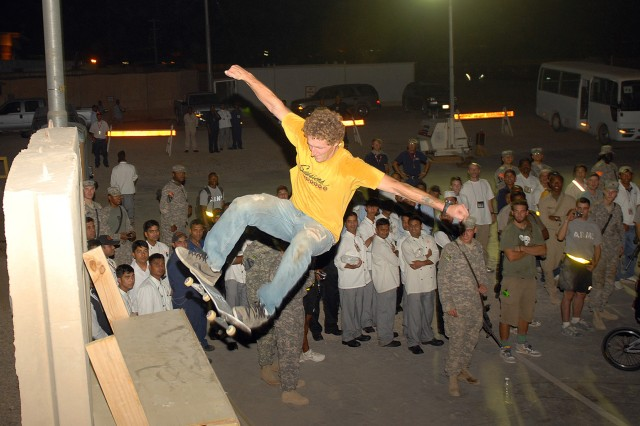 """CAMP LIBERTY, Iraq- Soldiers from Multi-National Division - Baghdad crowd around as Jud Heald, a pro skateboarder, from Joplin, Mo., performs during the """"Bikes Over Baghdad"""" BMX and skateboard exhibition tour at Camp Liberty, here, Sept. 9."""