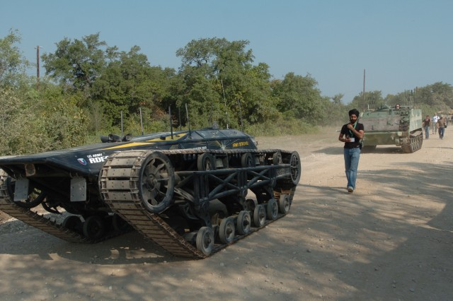 An autonomously operated truck follows the lead car, demonstrating its ability to conduct convoy operations during the Robotics Rodeo.