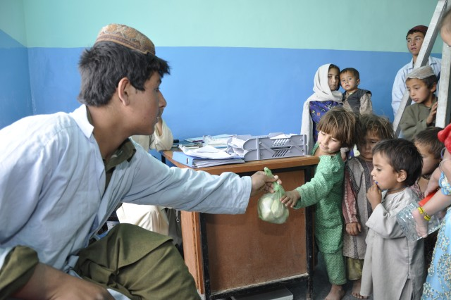 ZABUL PROVINCE, Afghanistan - A provincial hospital worker hands a child a food supplement meant to increase children's weight and appetite as part of the Strong Food program. The Ministry of Public Health with the help of the Provincial Reconstruction Team-Zabul created Strong Food to combat the leading causes of death for Afghan children under the age of five.