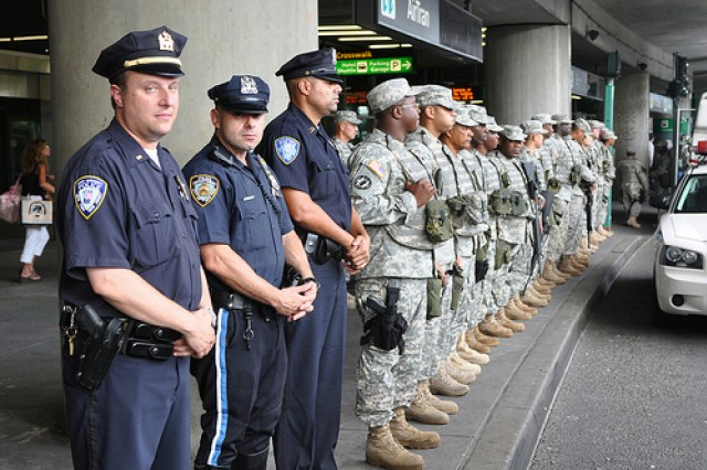 Members of the Port Authority Police Department and the New York City Police Department join National Guard Soldiers serving with Joint Task Force Empire Shield as they take a pause from their regular duties at New York's La Guardia Airport, Aug. 25, to honor wounded warriors arriving for the World Burn Congress in Manhattan.