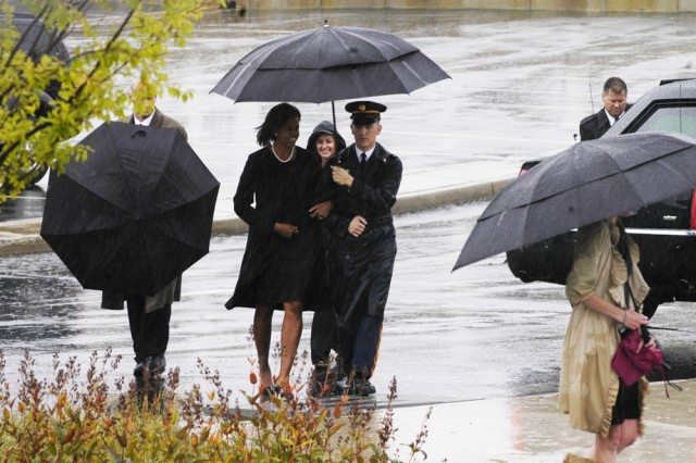 A Soldier escorts first lady Michelle Obama from the motorcade to the Pentagon Memorial just before the 9/11 Remembrance ceremony Sept. 11. President Barack Obama, Secretary of Defense Robert Gates and Adm. Michael Mullen, chairman of the Joint Chiefs of Staff, spoke at the event to families of the victims at the Pentagon.