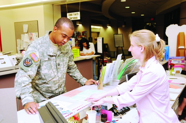 Capt. Patrick Hill, B Co., 1st Bn., 145th Avn. Regt., discusses travel plans with Information, Ticketing and Reservations (ITR) travel clerk Jenn Bartlett Aug. 31. ITR here received the biggest commission this fiscal year compared to ITRs Armywide.