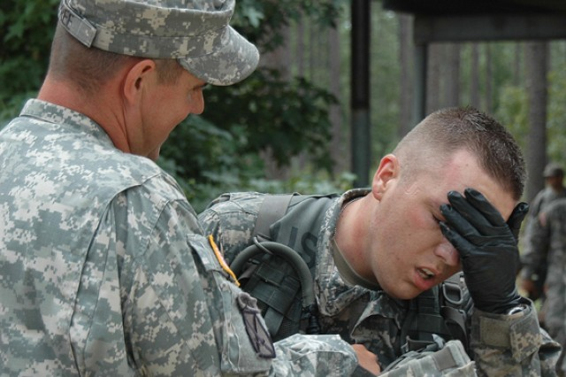Pfc. Terry Trinkella (right), a medic assigned to Headquarters and Headquarters Battery, 5th Battalion, 25th Field Artillery Regiment, 4th Infantry Brigade Combat Team, 10th Mountain Division, shows signs of exhaustion after completing a 45-minute trauma lane during annual certification testing at Castor 1 training area. Staff Sgt. James Depree, medical platoon sergeant for 2nd Battalion, 4th Infantry Regiment and medical certification grader, congratulates Trinkella for successfully completing the task and prepares to review Trinkella's performance.