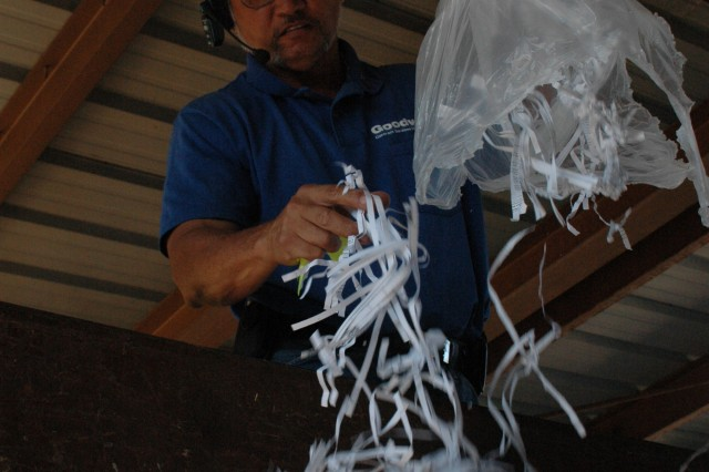 SCHOFIELD BARRACKS, Hawaii - Victor Mercado, supervisor, Army Recycling Center, drops shredded white paper in a transportation container for shipment to a processing plant. Money from the recycling program goes back into the Army community.