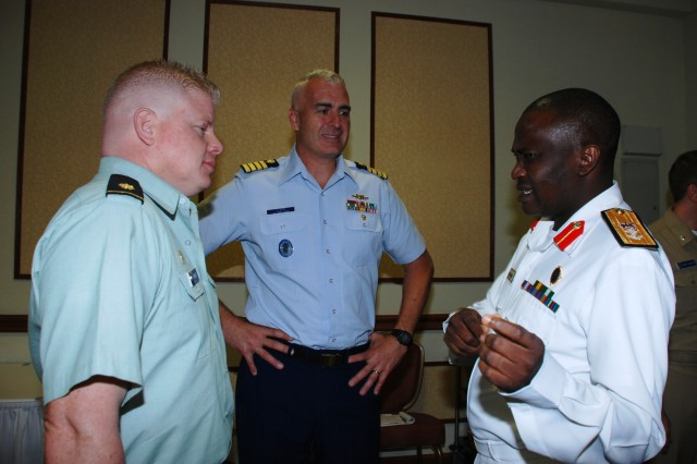 Nigerian Navy Commodore S.R. Shekoni, director of training for the Nigerian Navy headquarters (right), talks with Capt. Craig Barkley Lloyd, Coast Guard Liaison at U.S. Africa Command (center), and Maj. Jeff Price, bilateral affairs officer for the U.S. Embassy in Abuja, during a Theater Security Cooperation planning meeting, Sept. 10, 2009, in Stuttgart, Germany. The Nigerian delegation and representatives from U.S. Africa Command and its component organizations joined together to discuss their goals and objectives for fiscal year 2010-2012.