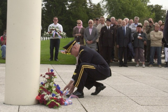 HENRI CHAPELLE, Belgium -- U.S. Army Europe Commander Gen. Carter Ham places a wreath at the base of a monument honoring the Soldiers buried at the American cemetery here in a ceremony Sept. 11 coinciding with the anniversary of terrorist attacks against America eight years ago.