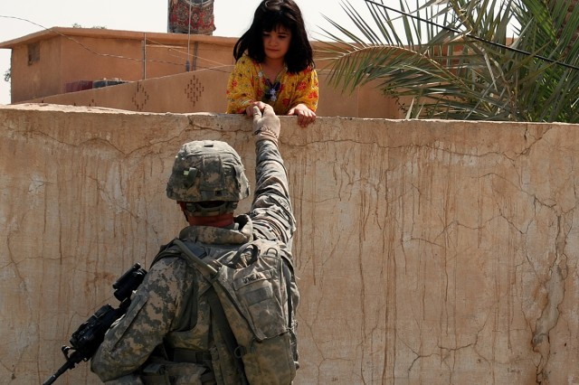 Staff Sgt. Kevin O'Neal, 277th Aviation Support Battalion, 10th Combat Aviation Brigade Quick Reaction Force platoon sergeant, shakes hands with a curious Iraq girl Aug. 4 while on mission to Al-Hasra. The QRF team is responsible for the security of Contingency Operating Base Speicher, but acts as ambassadors of peace during their frequent interaction with the locals.