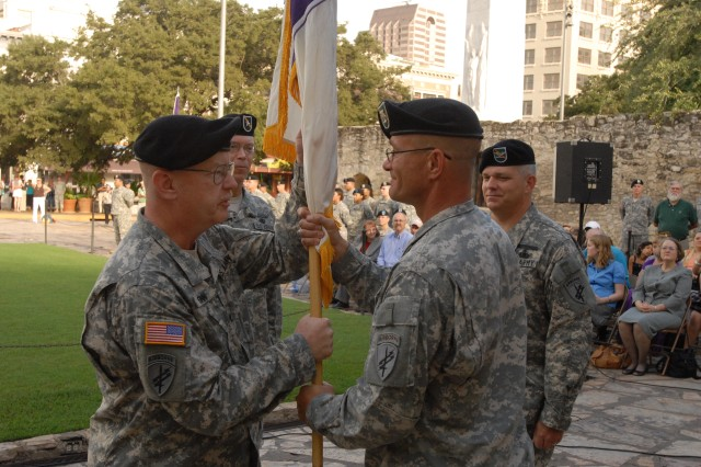 Col. Michael Finn, outgoing commander of the 321st Civil Affairs Brigade in San Antonio, accepts the brigade colors from Command Sgt. Maj. Terry Longsworth during the Army Reserve unit's change of command ceremony, Sept. 13, outside the Alamo in downtown San Antonio. Finn, who filled in as the unit's acting commander for several months, returned to his position as the 321's deputy commander upon passing the brigade colors over to Col. Kenneth Moore, the unit's new full-time commander. The 321st is part of the U.S. Army Civil Affairs.