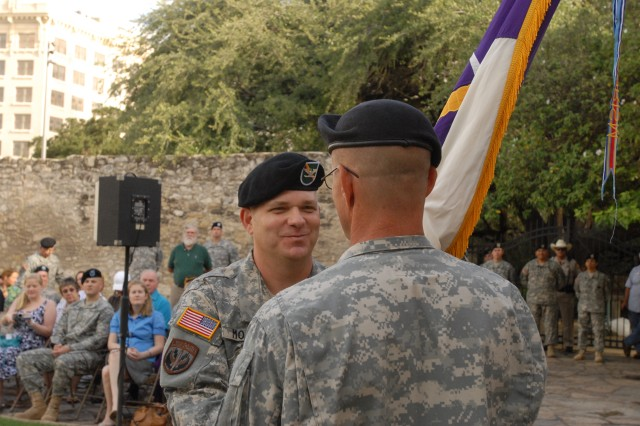 Col. Kenneth Moore hands the unit colors of San Antonio's 321st Civil Affairs Brigade over to Command Sgt. Maj. Terry Longsworth immediately after being officially recognized as the brigade's new commander in a change of command ceremony, Sept. 13, outside the Alamo. The Alamo, a symbol of national and Texan pride, is prominent in the 321's crest. The 321st, an Army Reserve unit located on Fort Sam Houston, is part of the U.S. Army Civil Affairs.