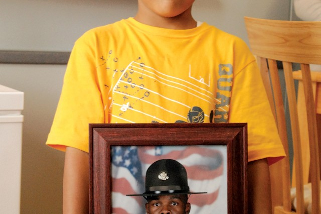Jovanni Addison, 7, displays a photo of his father, who is deployed to Afghanistan.