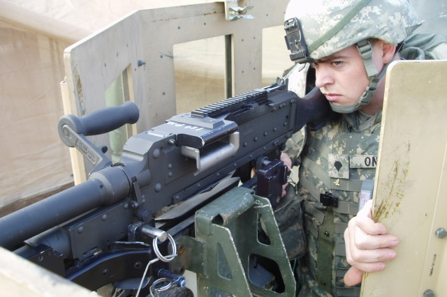 A Soldier sits with an M240B machine gun mounted in the Light Machine Gun and Medium Machine Gun Cradle. While there is no ammunition in this cradle, when in use, a standard 100 or 200-round 5.56 mm ammunition container or a 200-round 7.62 mm steel ammunition can sits in the cradle to help feed ammunition into the weapon without it getting tangled.