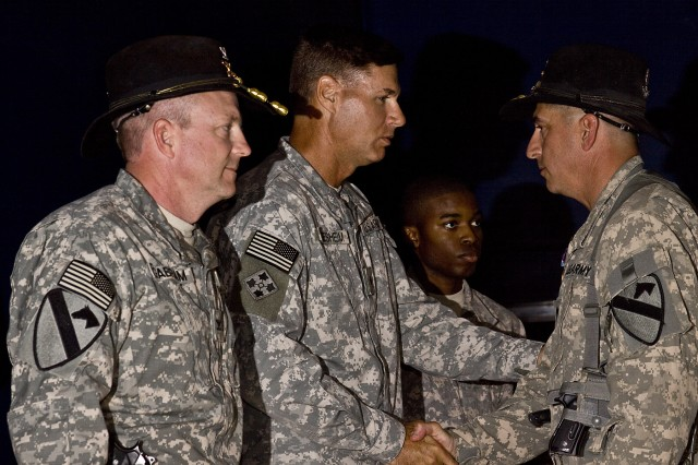 CAMP TAJI, Iraq-During an awards ceremony held Sept. 12, at Camp Taji, Iraq, Brig. Gen. Frederick Rudesheim (center), the deputy commanding general of support, 1st Cavalry Division, Multi-National Division - Baghdad, and Col. Douglas Gabram (left), from Cleveland, Ohio, the commander of the 1st Air Cavalry Brigade, 1st Cav. Div., MND - B, present the Humanitarian Service Medal to Lt. Col. Ralph Litscher (right), from Half Moon Bay, Calif., commander of 2nd Battalion, 227th Aviation Regiment, 1st ACB, for the support he and his battalion provided during Hurricane Ike.