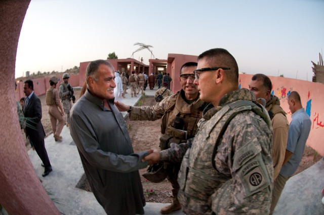Col. Matthew Lopez, commander of Marine Regimental Combat Team 6, introduces the Karmah education inspector to Col. Mark Stammer, commander of 1st Brigade, 82nd Airborne Division, at the opening of the Karmah School for Girls, Sept. 9. Stammer's brigade of paratroopers is continuing the Marine's partnerships with Iraqi Security Forces and local officials to ensure that school and water projects are completed.