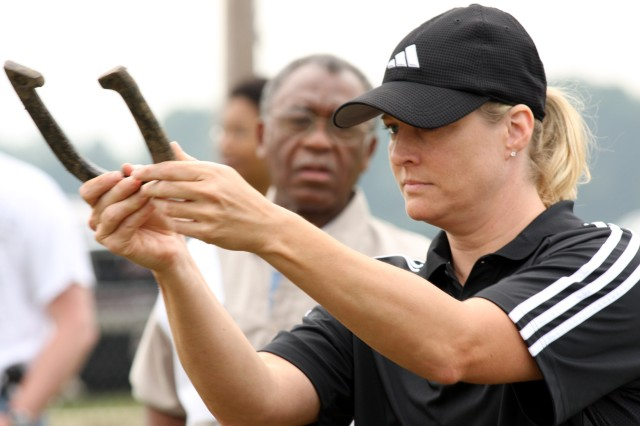 Dottie White, focuses on tossing a ringer at the horseshoe competition, as her opponent, Melvin Kelley, looks on during USASMDC/ARSTRAT's organizational day at the Rustic Lodge on Redstone Arsenal, Ala., Sept. 10.