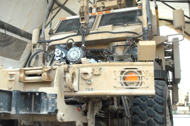 CAMP LIBERTY, Iraq - All-wheel mechanic, Spc. Catlynn Kovacs, from Colorado Springs, Colo., assigned to Headquarters Support Company, Division Special Troops Battalion, 1st Cavalry Division, works to install a new engine on a Mine-Resistant Ambush-Protected vehicle, here, Sept. 9.  The engine is held in place from a hook attached to a crane.  Mechanics must stabilize the engine by mounting it in place.  Maverick mechanics will package the older engine and ship it out for repair.