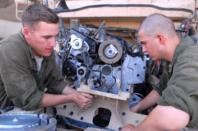 CAMP LIBERTY, Iraq - All-wheel vehicle mechanics, Spc. Harold Rust (left), from Helena, Mont. and Spc. Catlynn Kovacs (right), from Colorado Springs, Colo., both assigned to Headquarters Support Company, Division Special Troops Battalion, 1st Cavalry Division, place a radiator mount next to the new engine of a Mine-Resistant Ambush-Protected vehicle, here, Sept. 9.