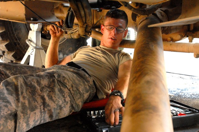 CAMP LIBERTY, Iraq - Spc. Joshua Tisdale, an all-wheel mechanic from Pekin, Ill., assigned to Headquarters Support Company, Division Special Troops Battalion, 1st Cavalry Division, hooks up wires to the starter, here, Sept. 9.  Disassembling and reassembling wiring for the starter is part of the process that is included in replacing an engine, said Tisdale.