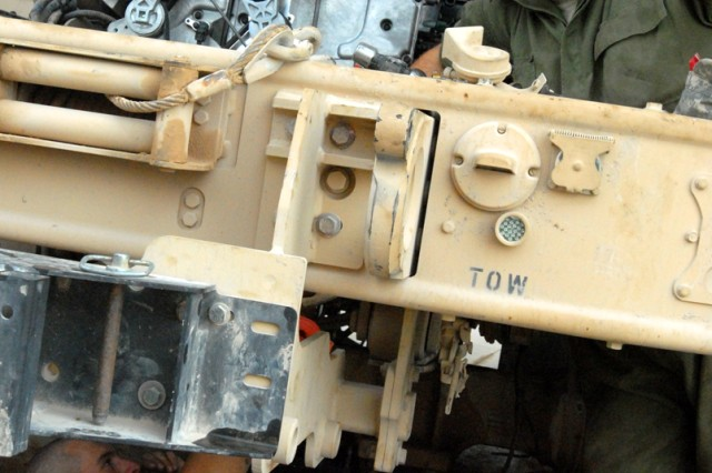 CAMP LIBERTY, Iraq - All-wheel mechanics, Spc. Catlynn Kovacs (bottom), from Colorado Springs, Colo., and Spc. Harold Rust (top), from Helena, Mont., both assigned to Headquarters Support Company, Division Special Troops Battalion, 1st Cavalry Division, work together to install a new engine on a Mine-Resistant Ambush-Protected vehicle, here, Sept. 9.  Often, the mechanics are talking to each other, one under the belly and the other atop the engine in order to assemble and disassemble key components.