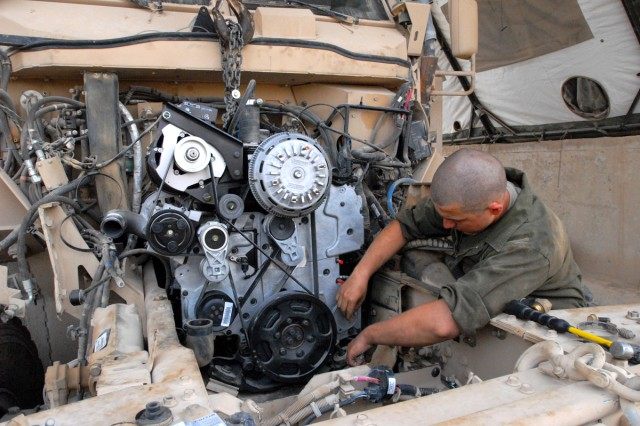 "CAMP LIBERTY, Iraq - All-wheel mechanic, Spc. Catlynn Kovacs, from Colorado Springs, Colo., assigned to Headquarters Support Company, Division Special Troops Battalion, 1st Cavalry Division, checks each part of a new engine on a Mine-Resistant Ambush-Protected vehicle, here, Sept. 9.  ""It's a big job, we use our experience to piece things together as we go,"" said Kovacs.  ""We're always learning new things because the vehicles are changing and evolving."""