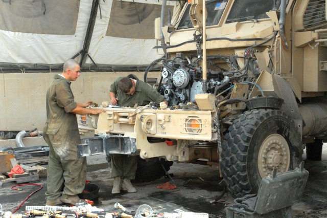 CAMP LIBERTY, Iraq - All-wheel mechanics assess the situation and begin the process of bolting and placing all the wires and parts of a new engine in order for the Mine Resistant Ambush Protected vehicle to run efficiently, here, Sept.9.