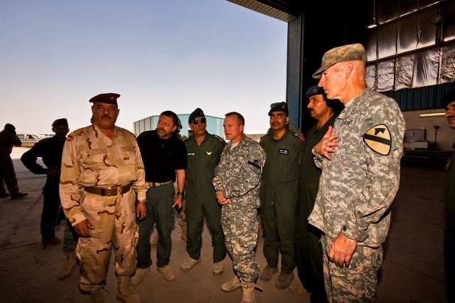 CAMP TAJI, Iraq-Showing sincere appreciation, Maj. Gen. Daniel Bolger (right), commanding general of the 1st Cavalry Division and Multi-National Division - Baghdad, thanks Gen. Abud Qanbar Hashim al-Maliki (left), commanding general, Baghdad Operations Command, for attending a meeting to show the capabilities of the Iraqi Air Force and how they can benefit the Iraqi Army.  Col. Douglas Gabram (center), commander of the 1st Air Cavalry Brigade, 1st Cav. Div., MND - B,hosted the Sept. 10 meeting along with Iraqi Air Force Brig. Gen. Nadhem Lafte al-Ajwdi (center with sunglasses), commander of al-Taji Airfield.