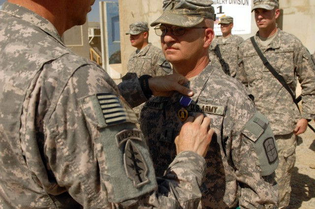 """CAMP LIBERTY, Iraq - First Lt. Frank Sarratt, executive officer of the 211th Mobile Public Affairs Detachment, Division Special Troops Battalion, 1st Cavalry Division, receives a Purple Heart and the Combat Action Badge from DSTB commander, Lt. Col. Matthew Karres, during a ceremony, here, Sept. 11. Sarratt, a native of Plano, Texas, was wounded in an improvised explosive device attack last month. Karres said presenting the awards on the anniversary of the Sept. 11 terrorist attacks against the United States was appropriate. """"I like doing the ceremonies out here, because it is dusty and dirty and that's what we're about,"""" he said. """"This symbolizes the reality of what we're doing here. It's about combat, it's about fighting the enemy."""""""