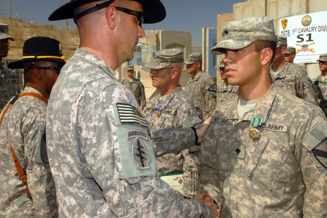 """CAMP LIBERTY, Iraq - Spc. Jacob Belonga, an infantryman from Muskegon, Mich., receives an Army Commendation Medal with a """"V"""" device for valor from Lt. Col. Matthew Karres, commander of Division Special Troops Battalion, 1st Cavalry Division, during a combat awards ceremony, here, Sept.11. Belonga was one of 15 """"Maverick"""" Battalion Soldiers who received various awards. Belonga manned a gun turret in a humvee and engaged an enemy machine gun nest. Belonga said receiving the award on the anniversary of the Sept. 11 terrorist attacks made the medal even more special. """"When Sept. 11 happened, I was in the 5th grade, and ever since then I wanted to join the Army, help out and serve my country,"""" said Belonga, who is assigned to D Troop, DSTB, 1st Cavalry Division. """"This is why I wanted to join and come over here."""""""