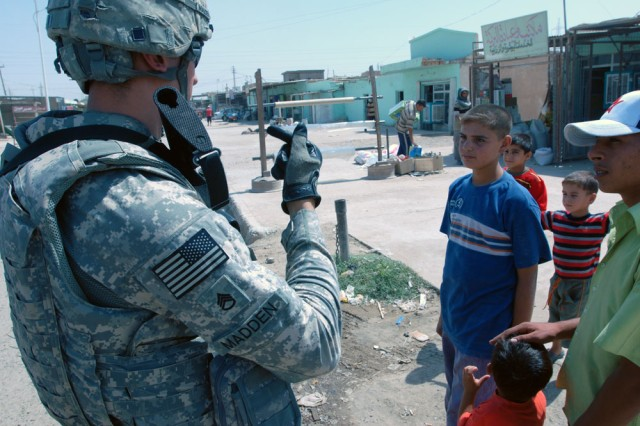 "TAJI, Iraq- Cambridge, Mass., native, Staff Sgt. Carlos Madden, a civil affairs team leader assigned to 1479 Civil Affairs Company, talks to local children while he and ""Dragons"" troops evaluate the progress of a public works project in Taji,"