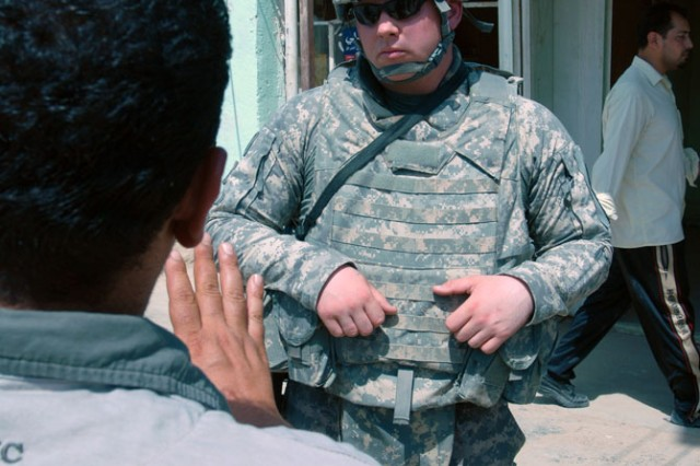 "TAJI, Iraq- Whitewater, Wis., native, Staff Sgt. Nicholas Lien, the civil capacity and essential services officer assigned to Headquarters and Headquarters Battery, 1st ""Dragon"" Battalion, 82nd Field Artillery Regiment, 1st Brigade Combat Team, 1st Cavalry Division, discusses the status of a public works project in the Taji Market with the manager of the project Sep. 10. ""We want to show that the money is not free and that there is work to be done,"" said Lien."