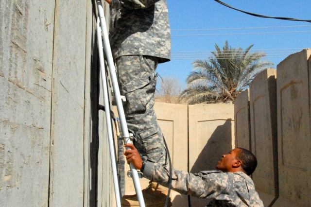 VICTORY BASE COMPLEX, Iraq - Sgt. Nekito Turner (right), cable section non-commissioned officer in charge, from Orlando, Fla., holds a ladder steady as Spc. Eugene Collado, a cable installer, from Koror, Republic of Palau, feeds cable through a duct system to another Soldier inside the building, here, Sept. 11.  The cable is being fed through to connect to a router in order to provide network service, including phone and internet connections.  Both Soldiers are part of Headquarters Support Company, Division Special Troops Battalion, 1st Cavalry Division.