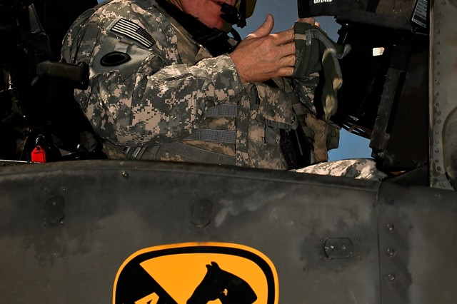CAMP TAJI, Iraq-Maj. Gen. James Hunt, deputy commanding general, Multi-National Corps - Iraq, prepares for his first flight in an AH-64D Apache attack helicopter during his visit to 1st Battalion, 227th Aviation Regiment, 1st Air Cavalry Brigade, 1st Cavalry Division, Multi-National Division - Baghdad, Sept. 11. Col. Douglas Gabram, from Cleveland, Ohio, commander, 1st ACB, wanted Hunt to get a better idea of an attack weapons team's capabilities by giving him hands-on experience from the air.