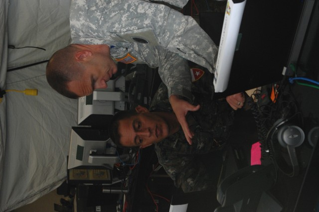 """Guatemalan Army Maj. Raul Pineda works alongside Maj. Brian Pederson, U.S. Army South Plans and Operations, at the Forward Command Post at Camp Bullis, Texas during PANAMAX 2009.  """"This is my first PANAMAX,"""" said Pineda.  """"We are sharing a lot of information when we do this exercise with so many countries.""""  PANAMAX 2009 is a multinational, joint forces exercise involving 20 countries and more than 4500 participants and observers exercising responses to any request from the Government of Panama to protect safe passage through the Panama Canal. (Arwen Consaul, U.S. Army South Public Affairs/Photo released)"""