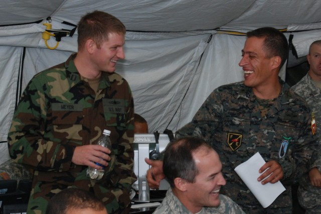 U.S. Navy Lt. Benjamin Meyer, Joint Forces Headquarters, Guatemalan Army Maj.  Raul Pineda and U.S. Air Force Lt.Col. Dan Jones (seated), 12th Air Force, take a break from the exercise to share a laugh about football at the Forward Command Post at Camp Bullis, Texas during PANAMAX 2009.  Working together and learning from each other during FA PANAMAX promotes trust and fosters willingness for continued collaboration and teamwork.  This opportunity strengthens our ability to operate together which ultimately strengthen security of the hemisphere.  (Arwen Consaul, U.S. Army South Public Affairs/Photo released)