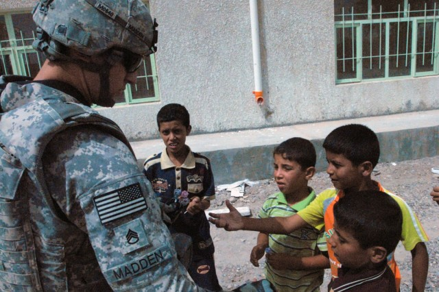 TAJI, Iraq- Cambridge, Mass., native, Staff Sgt. Carlos Madden, a civil affairs team leader assigned to 1479 Civil Affairs Company attached to the 1st Battalion, 82nd Field Artillery Regiment, 1st Brigade Combat Team, 1st Cavalry Division, hands lollipops to local children in a village north of Baghdad Sept. 10.  The Twin School construction project is scheduled to be completed by the end of September.