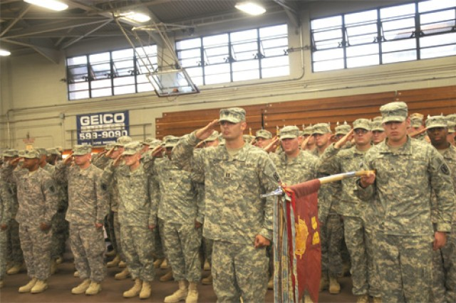 Capt. Jason Wood, (center) commander of troops, 89th Transportation Company, 6th Transportation Battalion, 7th Sustainment Brigade, presents arms during the national anthem at the company's welcome-home ceremony Monday evening at Anderson Field House. The group of about 140 Soldiers spent one year deployed in support of Operation Iraqi Freedom.
