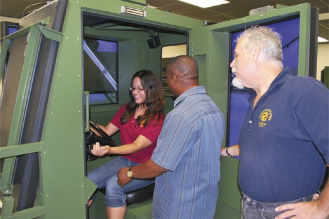 Dina Lina, curator, Transportation Museum, is being instructed by Robert Finnie, cargo handler instructor, U.S. Army Transportation School, on start-up procedures for the ATLAS Forklift Trainer. The ATLAS replicates the new forklift that is currently being fielded in units. All students spend 16 hours on the simulator before they transition to the actual equipment. This activity is designed to connect newly appointed civilian employees to the Army and T-School mission.