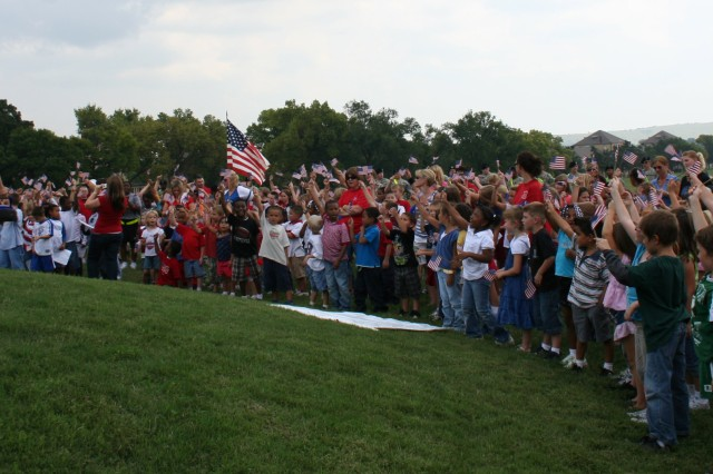 "Fort Riley Elementary School students sing ""God Bless America"" Sept. 11 at Scholfield Circle where they gathered to listen to Garrison Command Sgt. Maj. Ian Mann as part of their Freedom Walk."