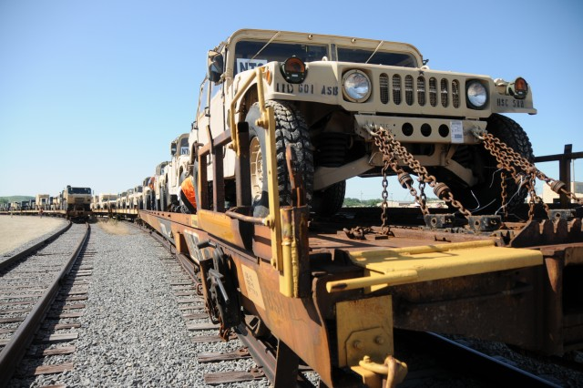 Unit equipment sits on top of railcars at Fort Riley's railhead, waiting to be transported to the National Training Center at Fort Irwin, Calif. Fort Riley has been using the railway system to transport unit equipment for deployments and training missions for decades, which in recent years has had to compete with other commercial traffic on the Union Pacific Railroad's main line. Currently, the railhead is undergoing a $15 million overhaul, which will add an additional 30,000 square feet of track to Fort Riley's railway system to expedite equipment transportation.