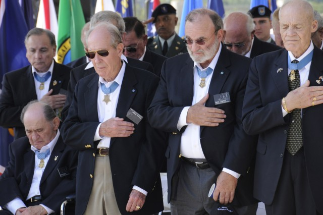 Medal of Honor recipients cover their hearts for a moment of silence during the opening ceremony of the Medal of Honor Convention at Soldier Field, Chicago, Ill., Sept 15.