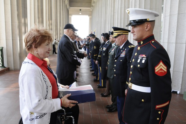 Medal of Honor recipients are presented with a flag from their military escorts, shortly before the opening ceremony of the Medal of Honor Convention at Soldier Field, Chicago, Ill., Sept 15.  The flags had been previously flown over Soldier Field on the anniversary date of the veteran receiving the Medal of Honor.
