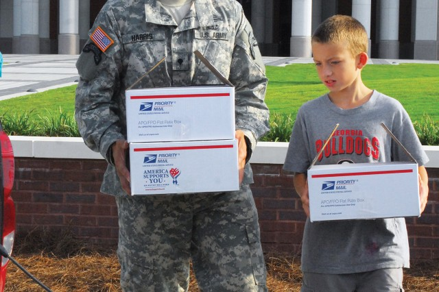 SPC Shane Harris and 10-year-old Bradley Cosgrove load care packages on the back of a truck to send to Soldiers in Iraq Friday at the National Infantry Museum.  Harris is matched as Bradley's big brother through the Big Brothers Big Sisters program.