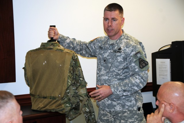 """Col. William E. Cole, a project manager with PM Soldier Protection and Individual Equipment, showcases a ghillie suit in the """"MultiCam"""" camouflage pattern during a media event Sept. 16, at the Pentagon."""