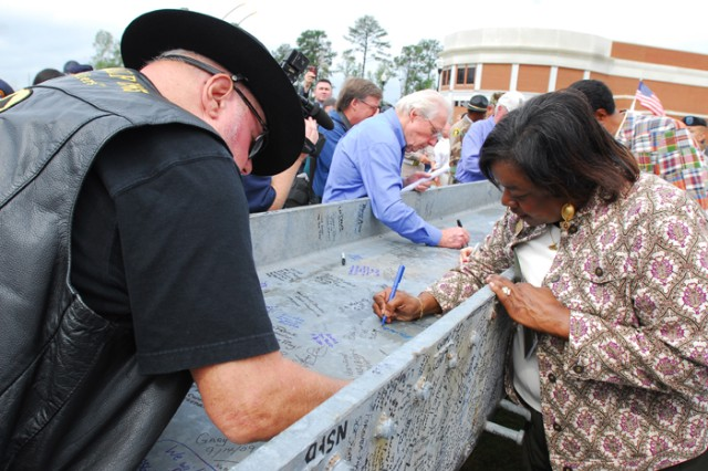 People gather to write messages on a steel support beam from the World Trade Center's North Tower at the unveiling ceremony Thursday.