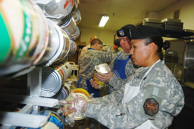 Headquarters and Headquarters Company, U.S. Army Garrison, Fort Sam Houston, 1st Sgt. Rosalba Chambers and Sgt. 1st Class James Peregory check for expired cans of food at the SAMMinistries shelter in San Antonio.