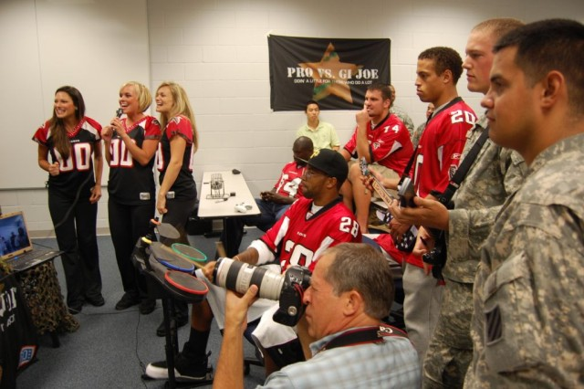 Soldiers from the 3rd Heavy Brigade Combat Team, 3rd Infantry Division, join Atlanta Falcon players and cheerleaders in Guitar Hero against deployed troops in Qatar and Afghanistan Sept. 15 in Flowery Branch, Ga.  The event was sponsored by non-profits Pro vs. G.I. Joe and the Uniformed Services Organization.