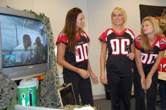 Cheerleaders from the Atlanta Falcons get ready to take the mic in a game of Guitar Hero versus deployed troops in Qatar and Afghanistan Sept. 15 at the Atlanta Falcon's Headquarters in Flowery Branch, Ga.  The event was sponsored by non-profits Pro vs. G.I. Joe and the Uniformed Services Organization.