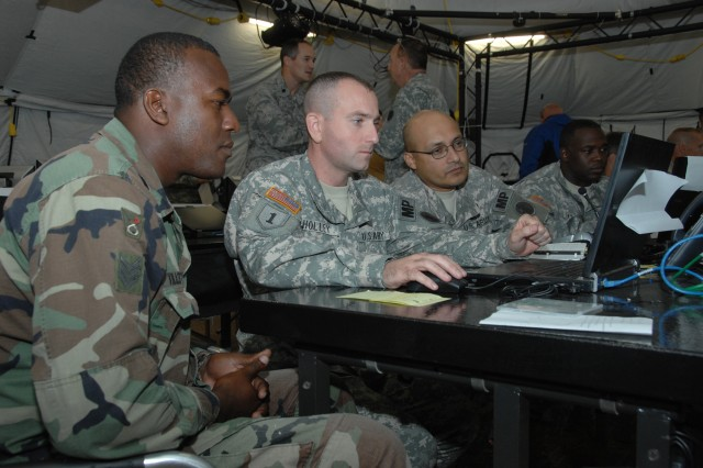 Maj. James Holley, from U.S. Army South's Provost Marshal's office, center, works alongside his counterpart from Belize Sgt. Joseph Tillet, left, during Fuerzas Aliadas PANAMAX 09 at Camp Bullis, Texas. PANA-MAX is an annual exercise involving military and inter-agency personnel, joint services and partner nation coalition personnel from various North, Central and South American and European countries focusing on the defense of the Panama Canal.
